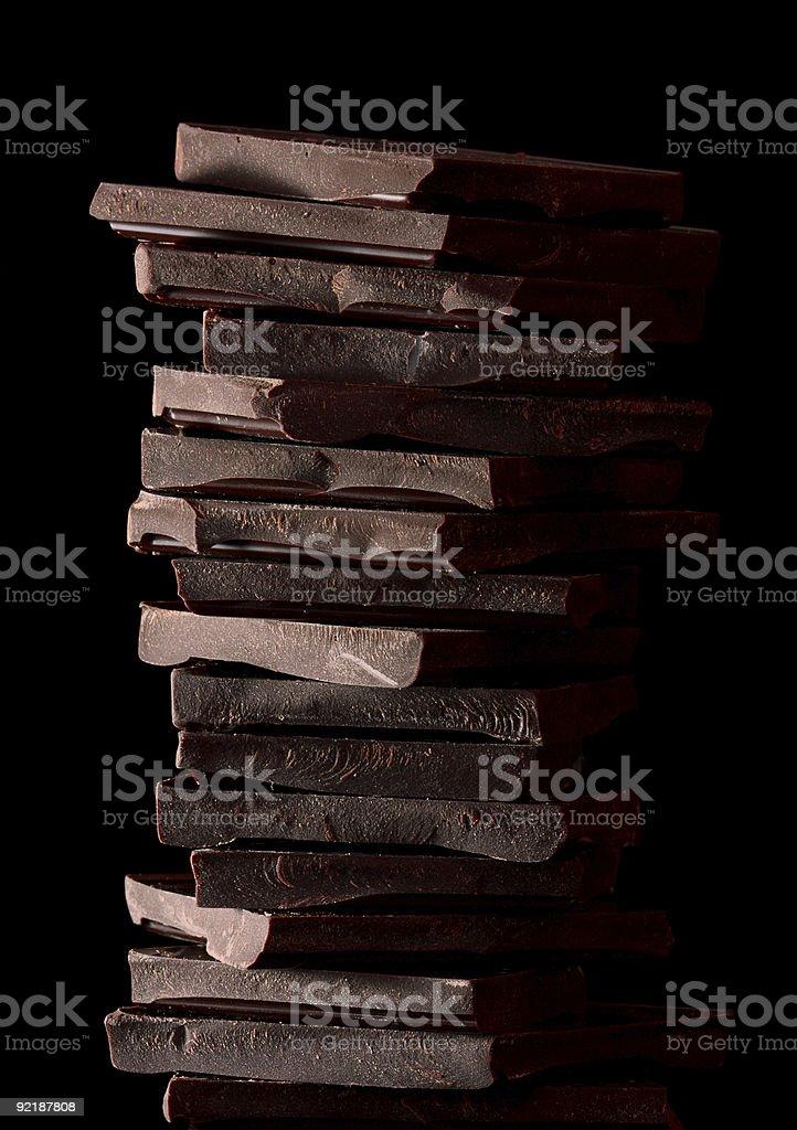 sweet food tower of dark chocolate pieces on black stock photo