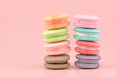 Sweet French macaroons cake (or macarons) with vintage pastel colored tone on pink background.