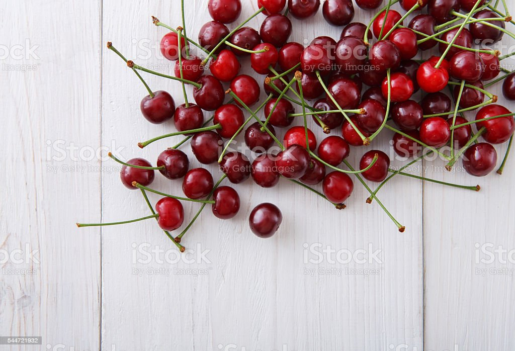 Sweet fresh cherries on white wood background stock photo