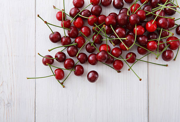 Sweet fresh cherries on white wood background stock photo