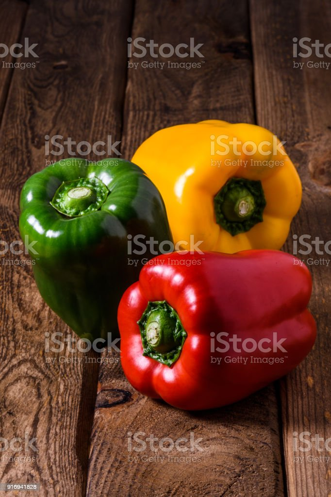 Sweet fresh red green yellow bell pepper on wooden table background stock photo