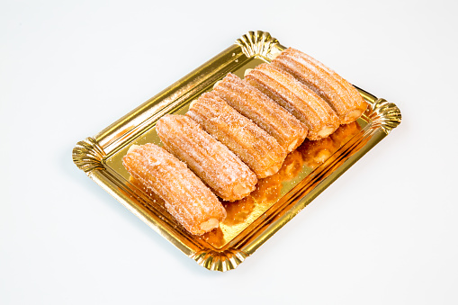 sweet fritter stuffed churro on a gold tray with white background