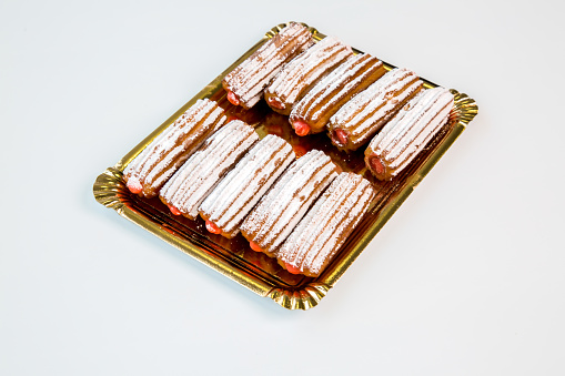 sweet strawberry fritter churros on a gold tray with white background