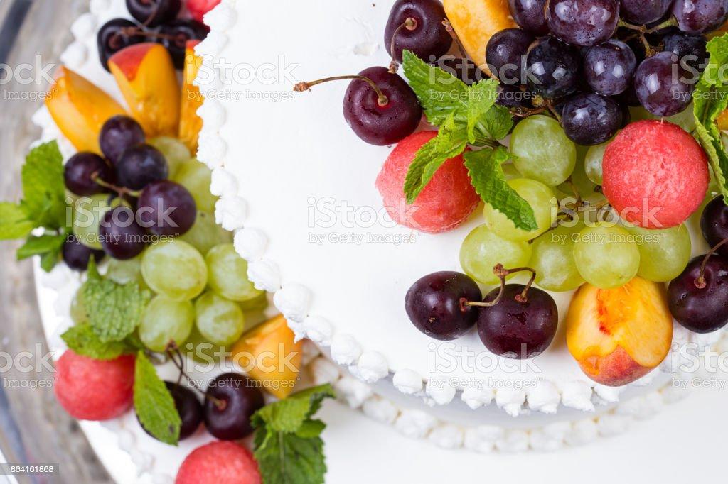 Sweet fruits and white wedding cake royalty-free stock photo