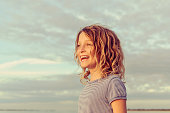 Adorable little girl with short wavy hair looks off into the distance in a cheerful, golden glowing portrait. She is a pretty 7 year old in a beautiful location, in a thoughtful and joyful moment