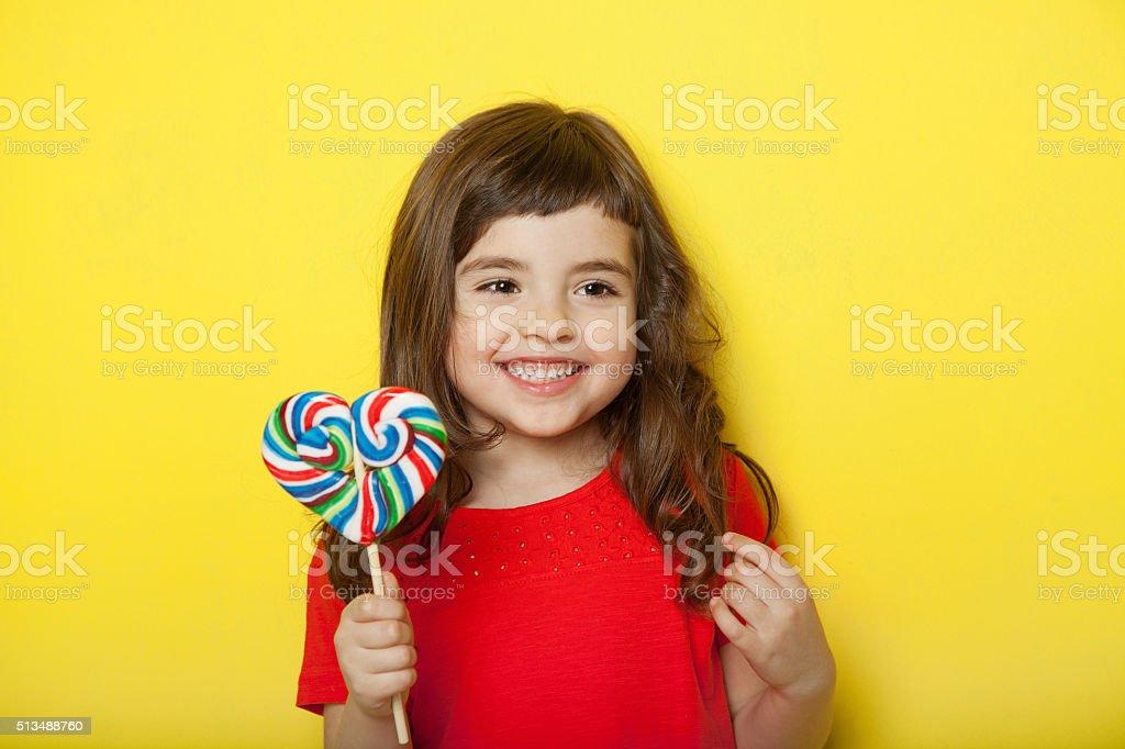 Sweet girl enjoying lollipop stock photo
