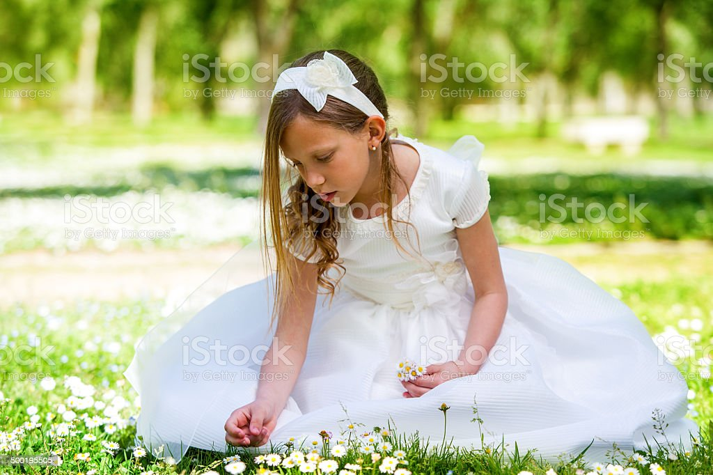 Sweet girl in white dress picking flowers. stock photo
