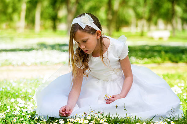 sweet girl in white dress picking flowers. - communion stock photos and pictures