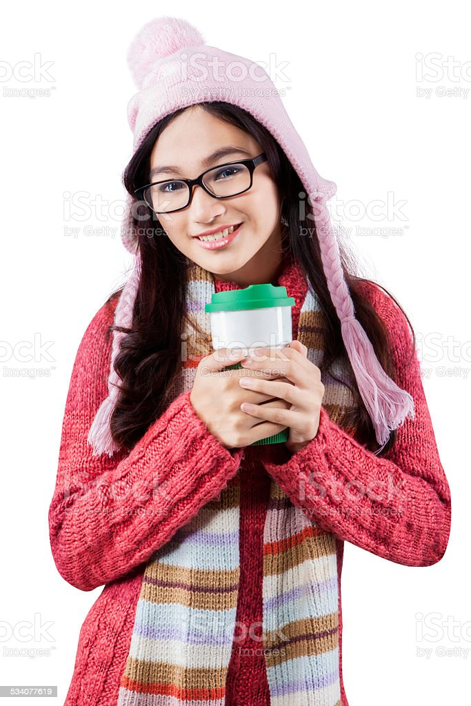 Sweet girl wearing warm clothes and holds hot drink stock photo