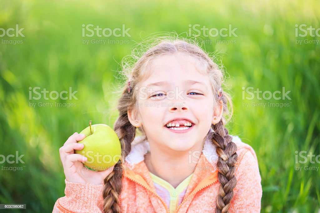 Sweet girl with a fallen tooth holding an apple stock photo