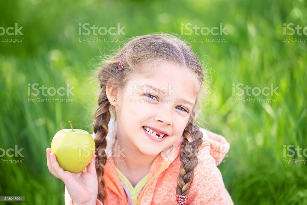 Sweet girl with a fallen toth holding an apple in stock photo