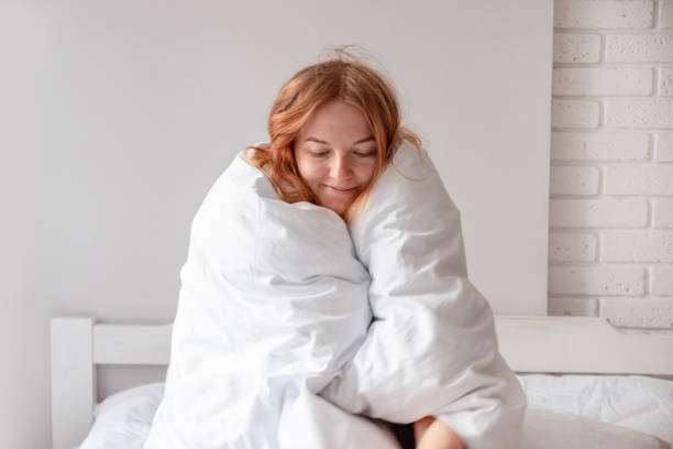 A sweet girl with golden hair is sitting on the bed and wrapped herself in a warm blanket. Good morning A sweet girl with golden hair is sitting on the bed and wrapped herself in a warm blanket. Good morning wrapped in a blanket stock pictures, royalty-free photos & images
