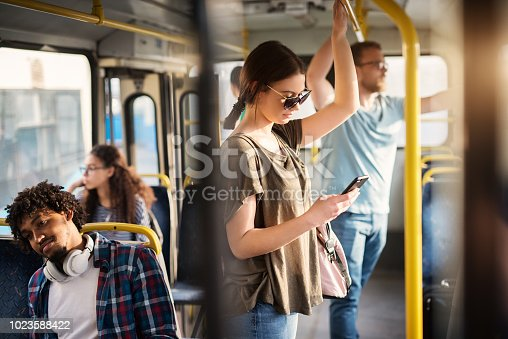 istock Sweet girl with sunglasses in using phone while standing in a bus. 1023588422