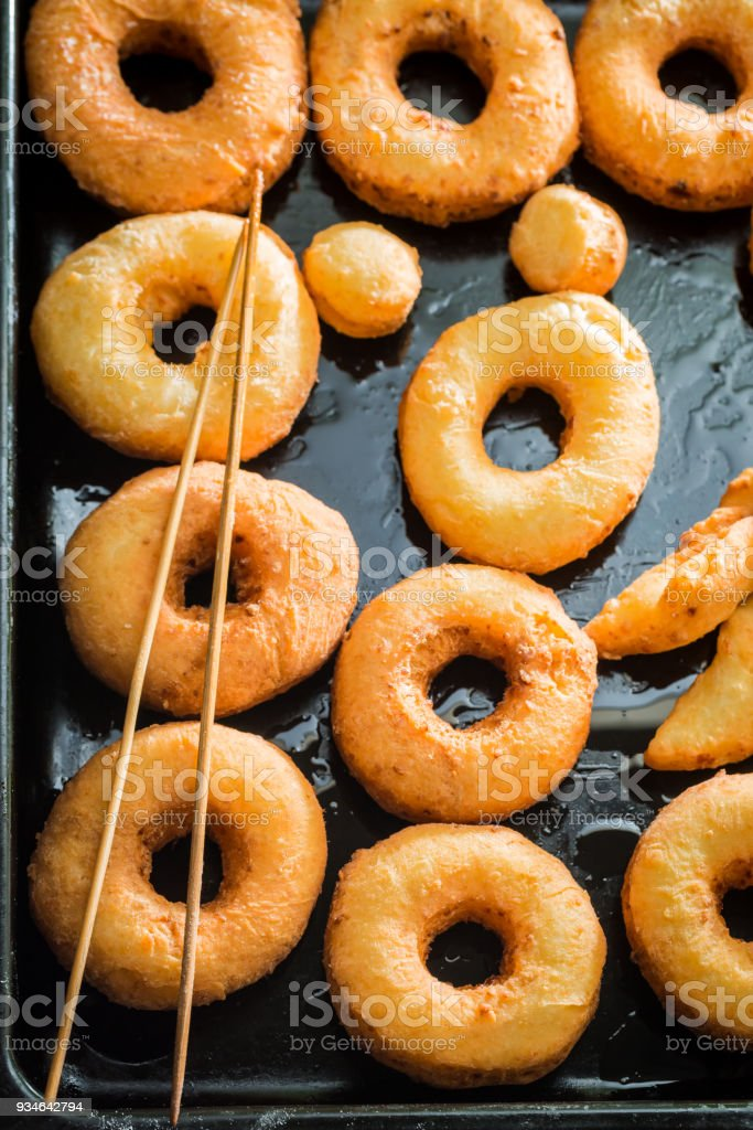 Sweet golden donuts freshly baked on black tray stock photo