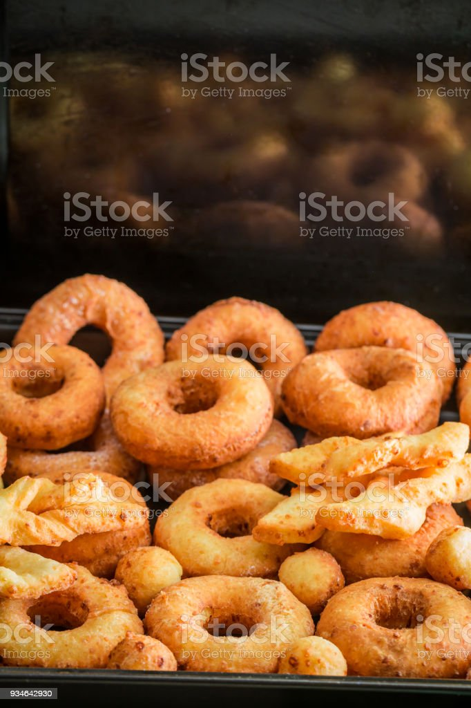 Sweet golden donuts with powdered sugar on black tray stock photo