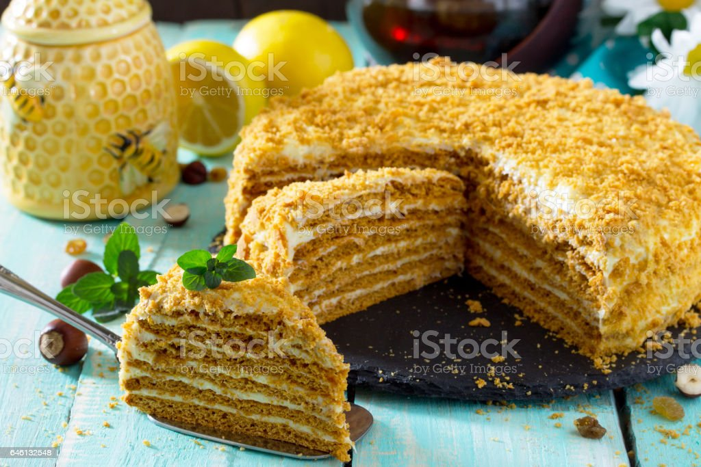 Sweet home layered honey cake on a wooden table with raisins and nuts. royalty-free stock photo