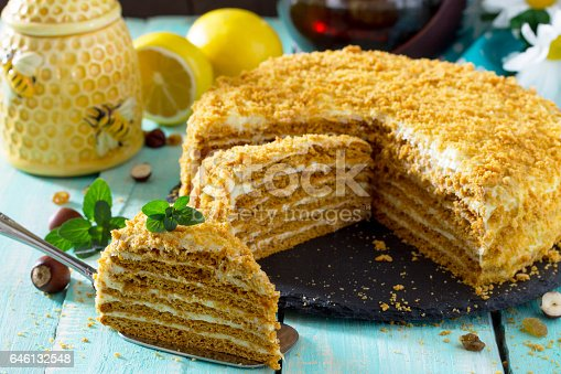 istock Sweet home layered honey cake on a wooden table with raisins and nuts. 646132548