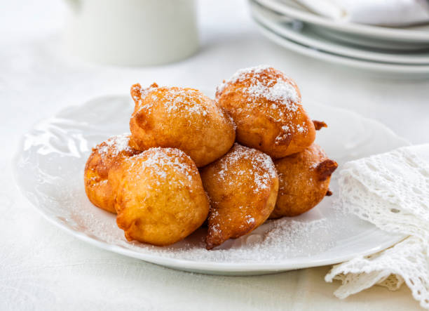 sweet homemade beignets covered with powdered sugar. - fritto foto e immagini stock