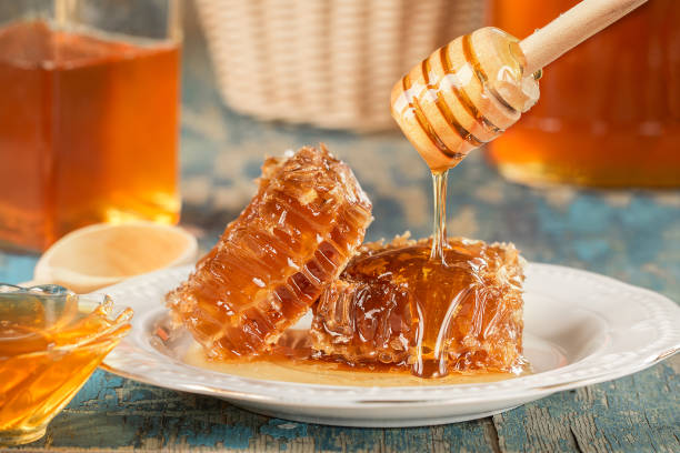 sweet honeycomb and wooden honey dripping - miele foto e immagini stock