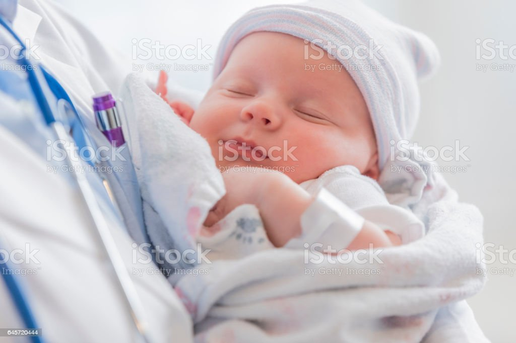 Sweet infant sleeps in doctor's arms stock photo