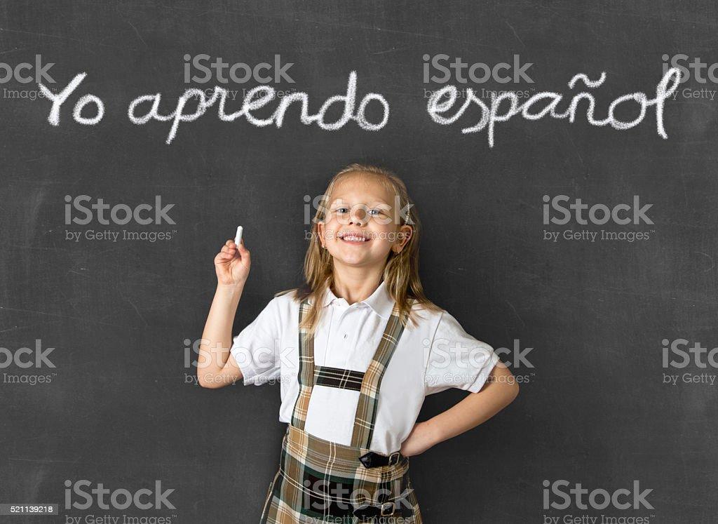 sweet junior schoolgirl happy  in children learning spanish language concept stock photo