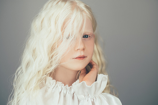 Sweet kid portrait. Natural beauty. Carefree childhood. Cute happy shy albino blonde little angel girl with curly hair blue eyes in white vintage blouse isolated on gray background.
