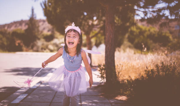 sweet little asian girl having fun outdoors in fairy queen costume - fairy wand stock photos and pictures