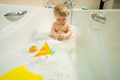 sweet little baby is bathing in the bath with toys