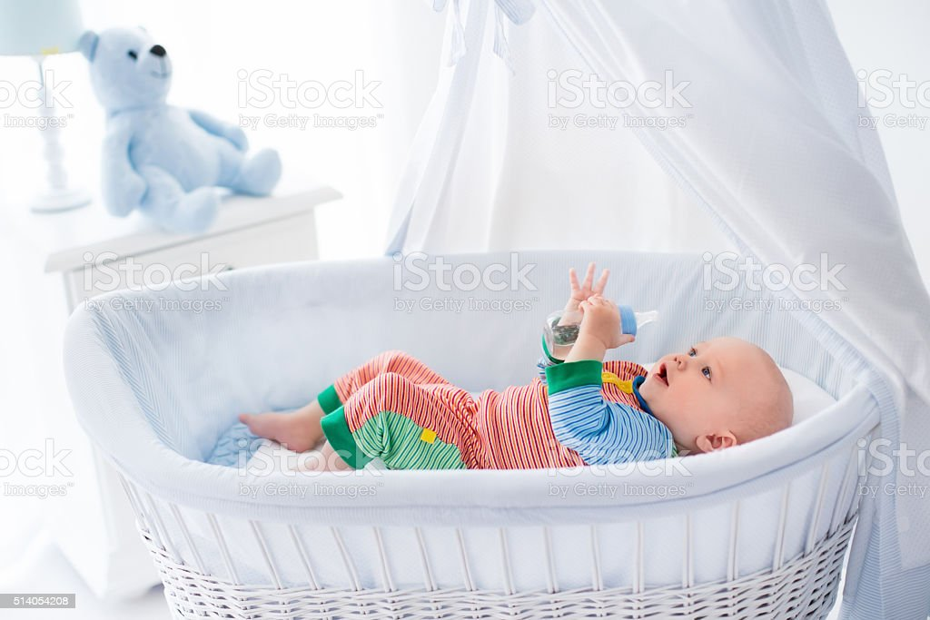 Sweet little baby with bottle in white bed foto