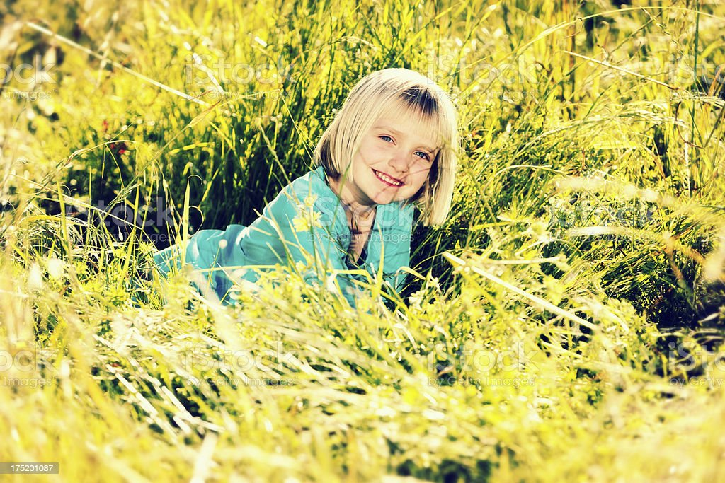 Sweet little blonde girl playing in grass, smiling happily stock photo