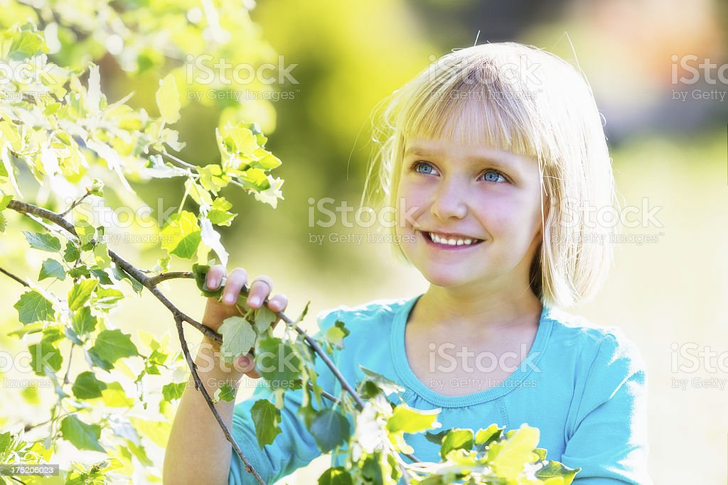 Sweet little blonde girl smiling at springtime tree stock photo