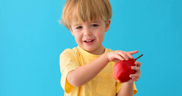 Sweet little boy smiles whith red pear stock photo