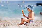 Sweet little child, boy, eating ice cream on the beach, summertime