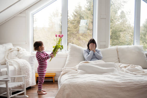 sweet little girl brings tulips flowers at bed during mother's day - manonallard stock photos and pictures