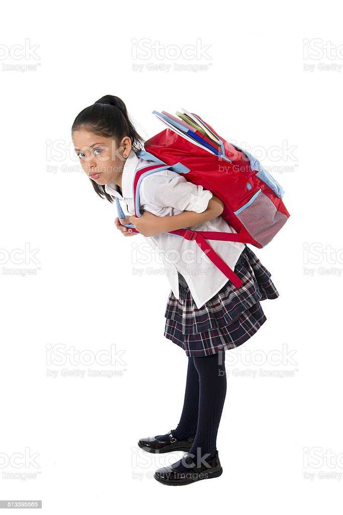 sweet little girl carrying very heavy backpack or schoolbag full stock photo