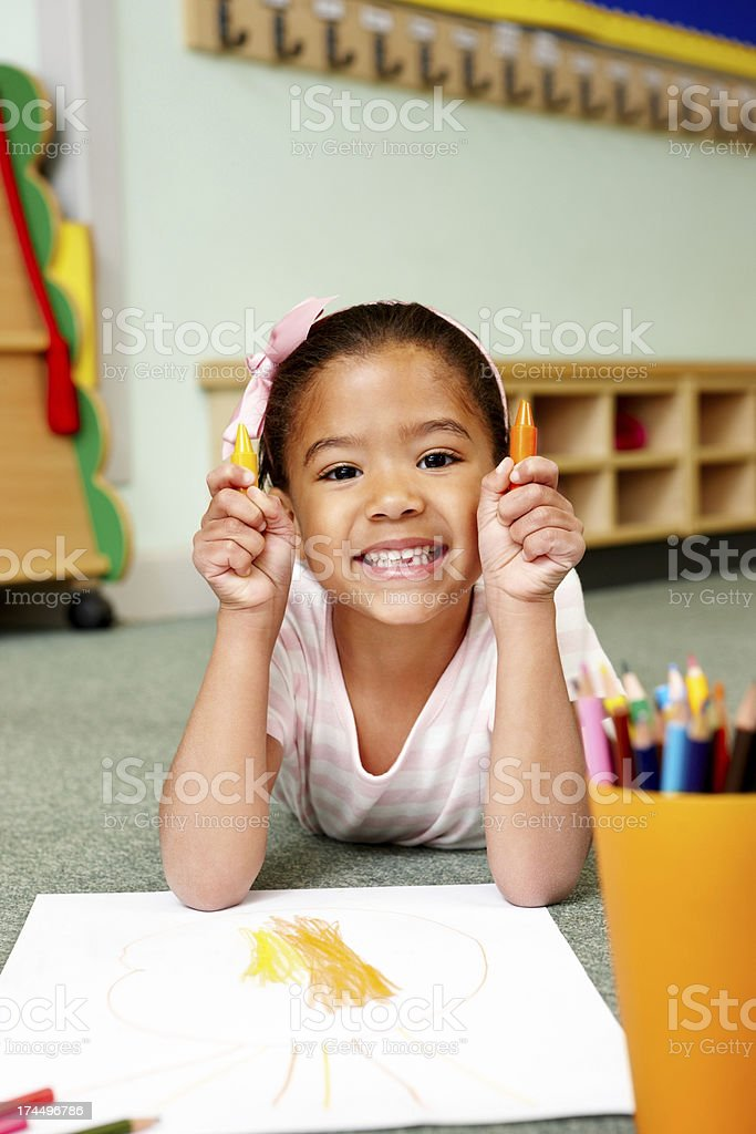 Sweet little girl drawing with crayons in classroom royalty-free stock photo