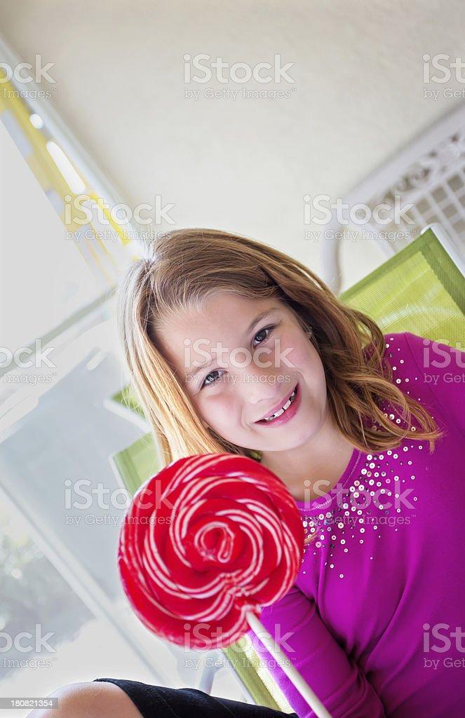 Sweet little girl holding a lollipop royalty-free stock photo