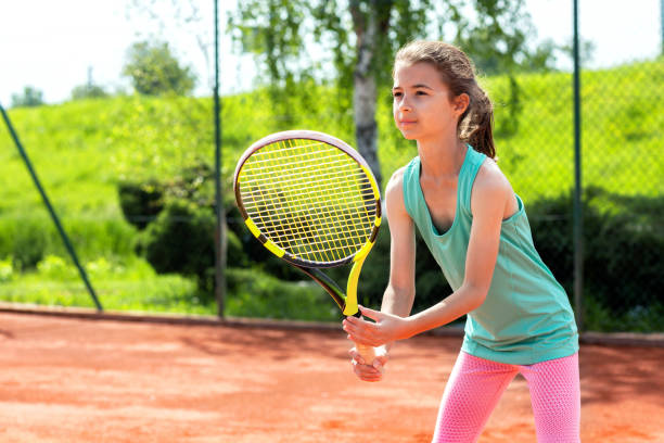 Sweet little girl holding a tennis racket stock photo