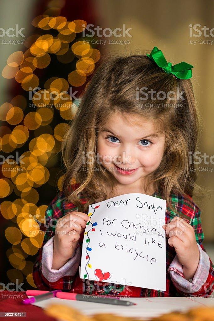 Sweet little girl holds up her letter to Santa stock photo