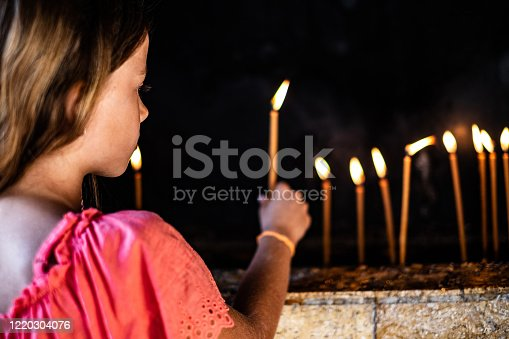 istock A sweet little girl in the church lit a candle. 1220304076