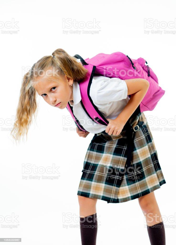Doce menina de uniforme, carregando a pesada mochila rosa grande ou mochila cheia, causando estresse e dor em volta devido ao excesso de peso isolado no fundo branco no conceito de educação escolar - foto de acervo