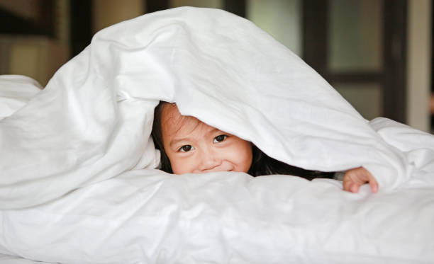 Sweet little girl looking at camera and smiling while lying in bed under the blanket. stock photo