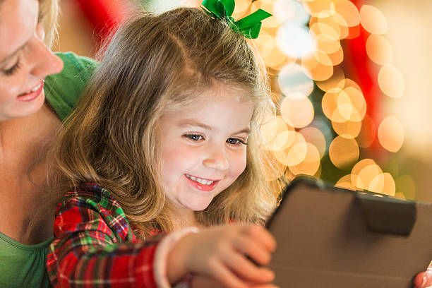 sweet little girl reads story on digital tablet at christmastime - lustige weihnachtsgeschichte stock-fotos und bilder