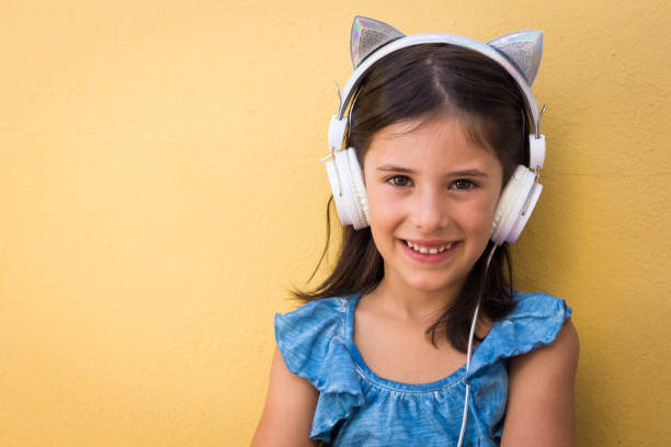 Sweet little girl sitting with cat ears headphones on stock photo