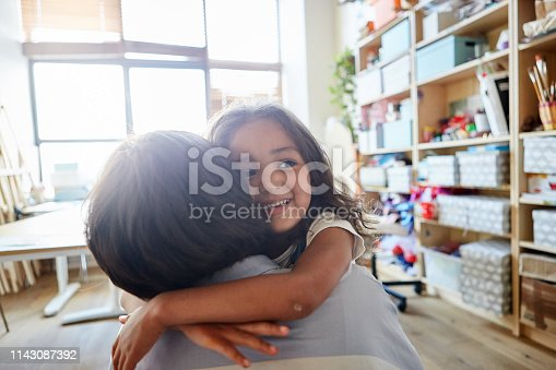 istock Sweet little girl smiling and embracing young teacher in classroom at art school 1143087392