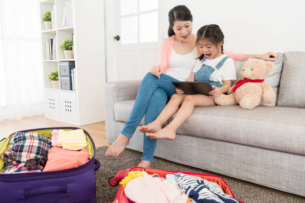 sweet little girl with mother sitting on sofa - happy mom packing some toys stock photos and pictures