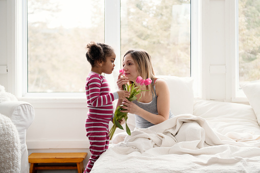 Sweet little mixed race girl of 4 years old old brings tulips flowers to bed to her mother during the mother's day. SHe is very proud to do that.  SHe wear pink pyjama. Photo can be use for Valentine's day, father's day, birthday. Photo was taken in Quebec Canada.