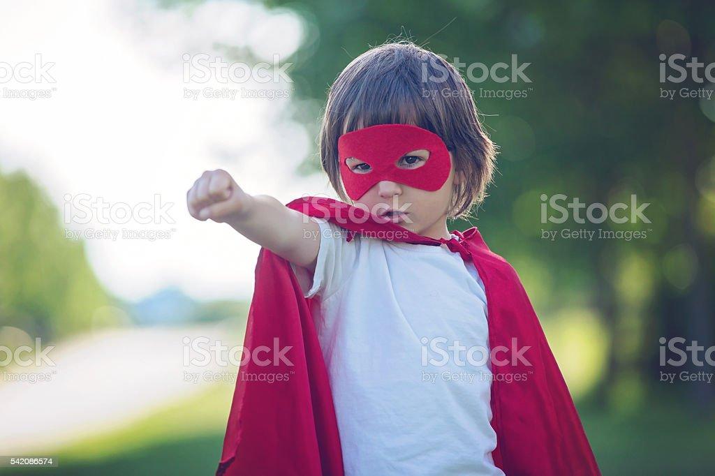Sweet little preschool boy, playing superhero in the park stock photo