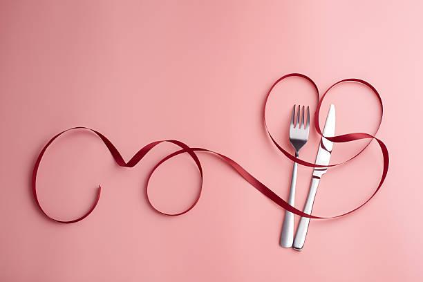 sweet love white dish, knife and fork around red ribbon - romantische karten stock-fotos und bilder