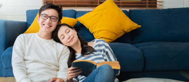 süße liebliche asiatische Familie paar sitzen sprechen gute Gespräch auf sofa im Wohnzimmer Haus Hintergrund – Foto